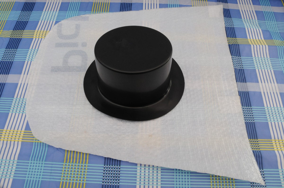 Black plastic supplies hat and template cut from a thick sheet of plastic