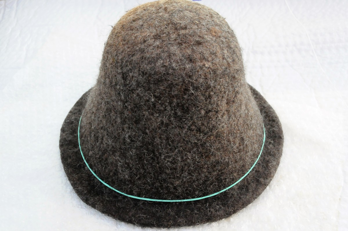 Put the hat onto the Hat Shaper, rub with hot soapy water, rinse and trim the brim.