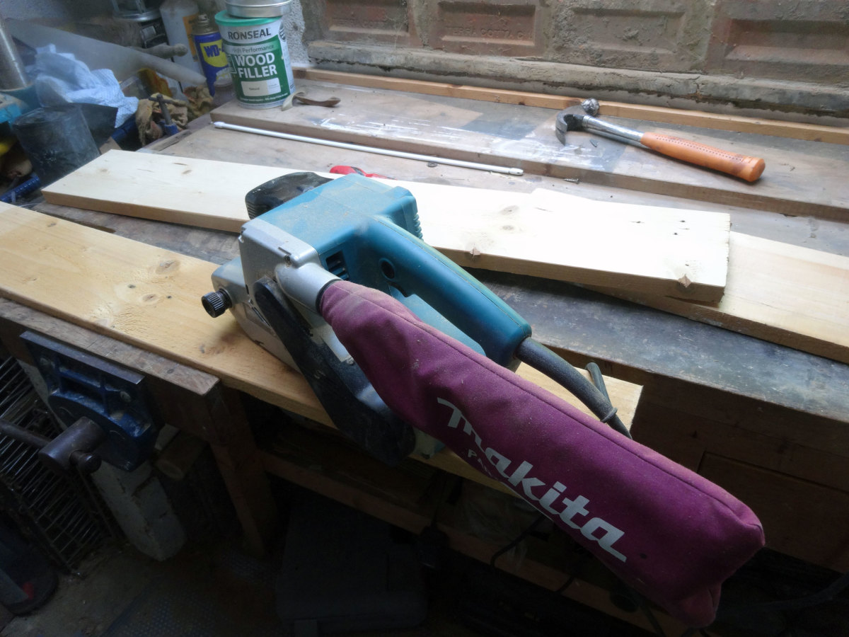 Using a belt sander to smooth rough wood.