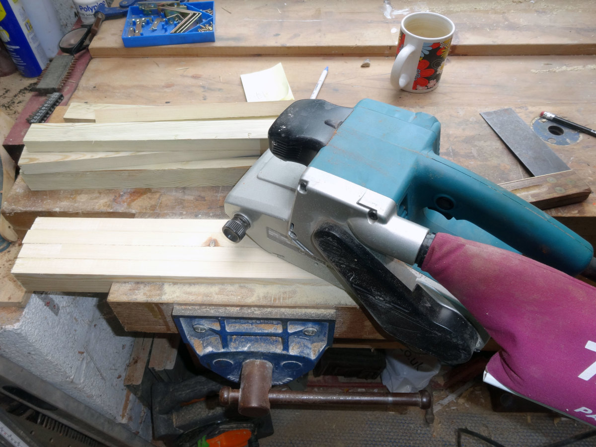 Belt sander to smooth down rough-cut roofing battens.
