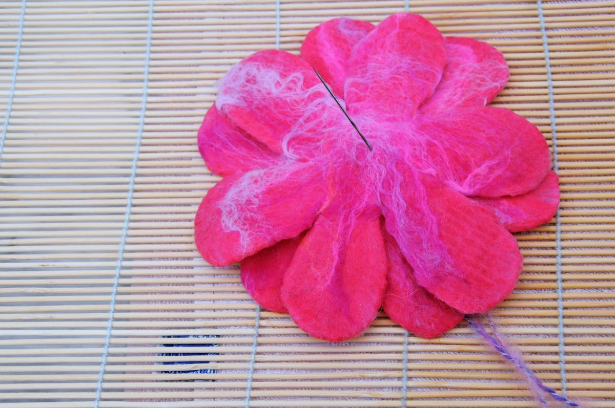 Stitch right through all 3 layers of the flower petals with a needle previously threaded with knitting wool