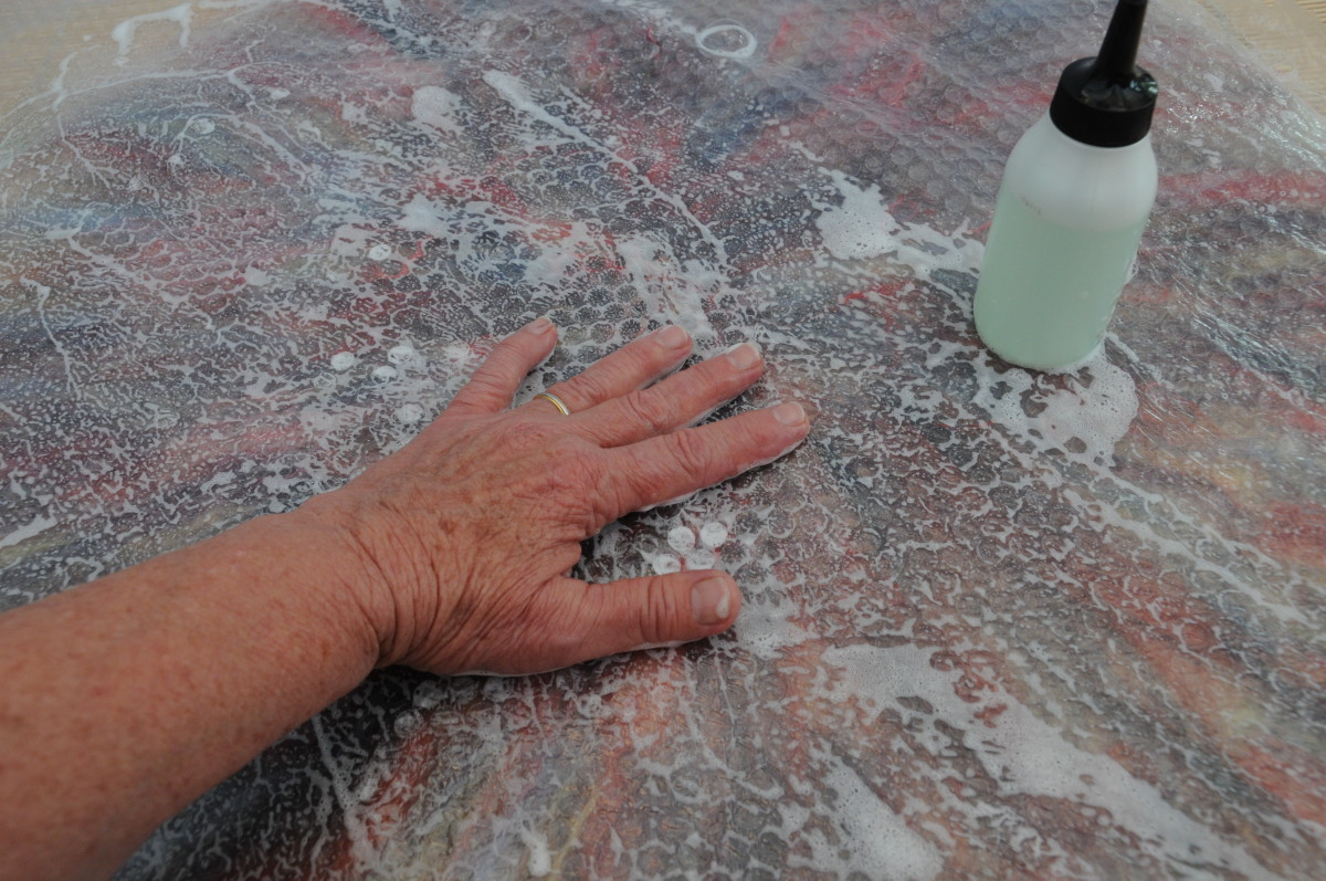 Rubbing the soapy surface to smooth out the fibers below