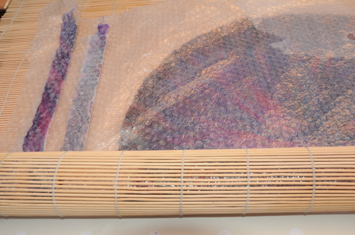 Add the 2 jacket or cape ties to the contents of the bamboo blind so that they can be rolled together.