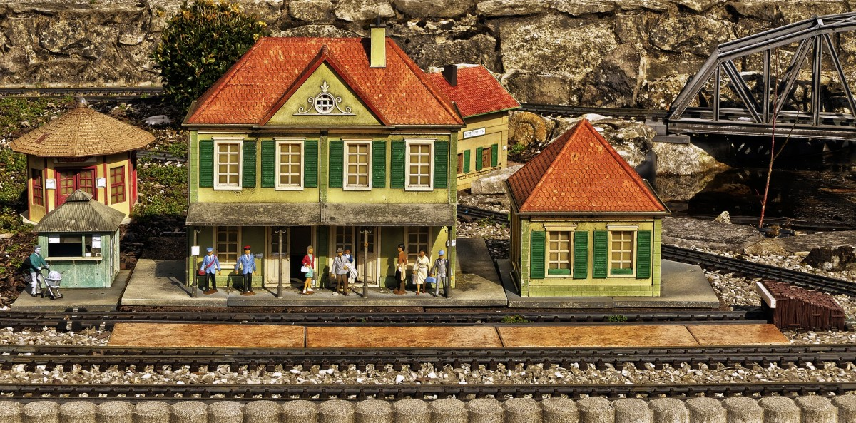 Model buildings are very popular for use in model train railways platforms. The train, all types of buildings, vehicles, and people are also built to scale whenever possible. This picture is an illustration of a train depot with its miniature people.