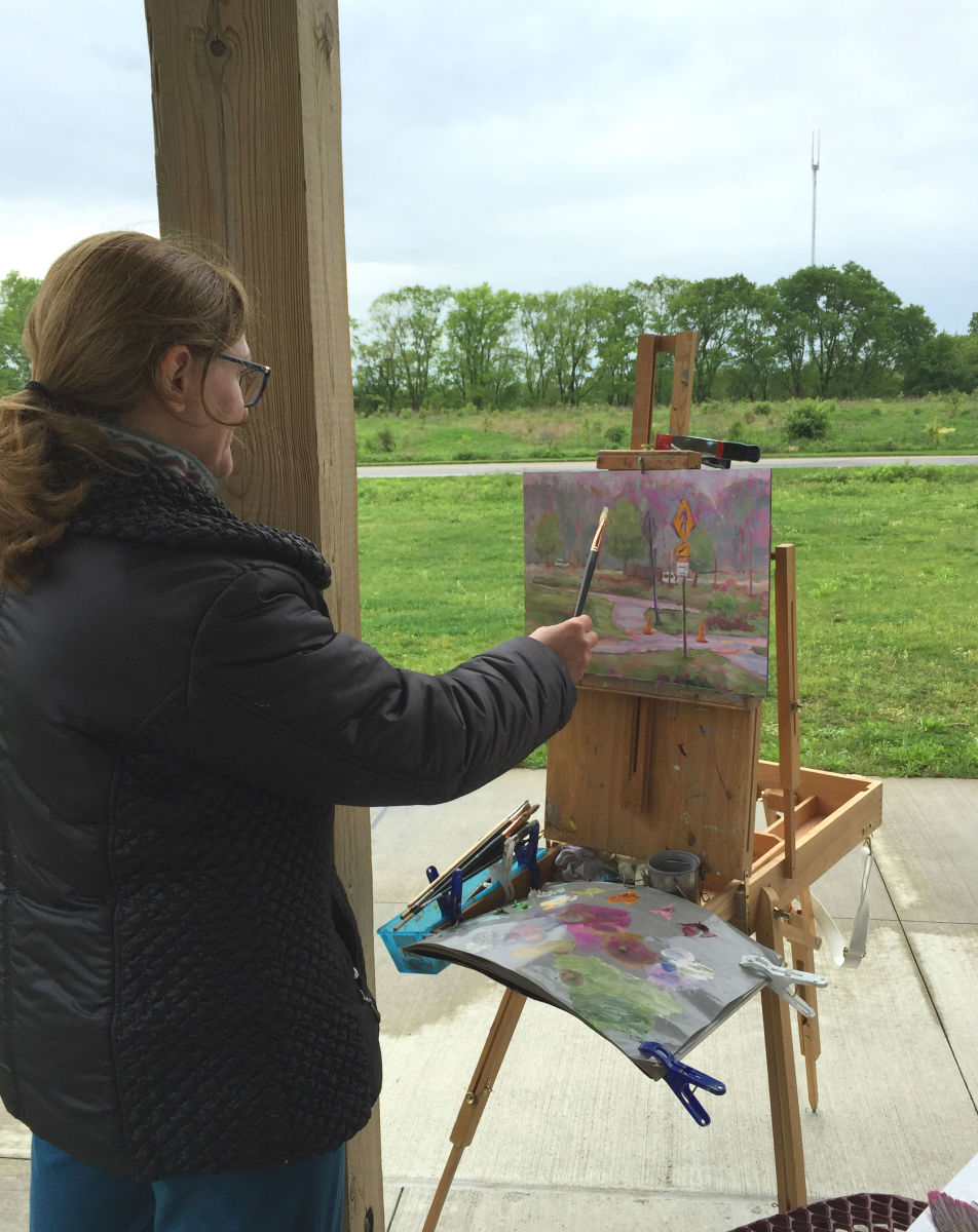 """Me again painting outdoors on a cold and rainy day. Finding shelter with a decent view became essential on that outing. The image source link is to my blog post """"Painting Outside Is Always a Challenge, but So Much Fun!"""""""