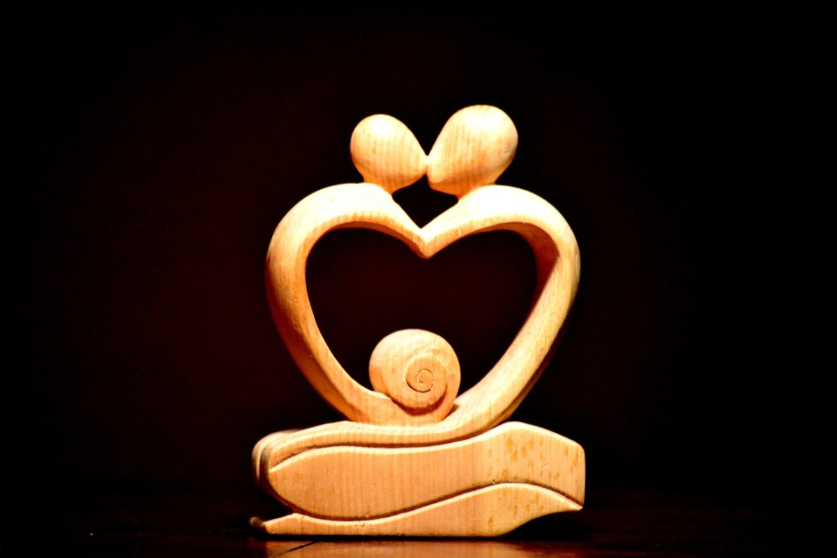 A carved wooden heart highlighted with a kissing couple.