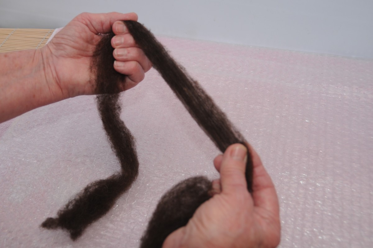 Stretching the fibers to the width required to make the finished dreadlocks.