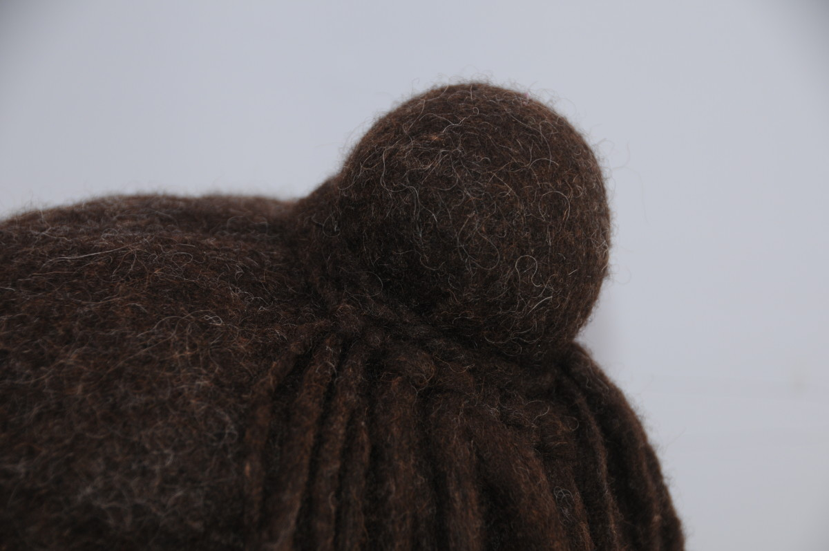 Make a plait using 3 dreadlocks.   Attach it loosely to the bun after removing the elastic band and then attach the other half of the dreadlocks to the plait.  Tie tightly around the bun.
