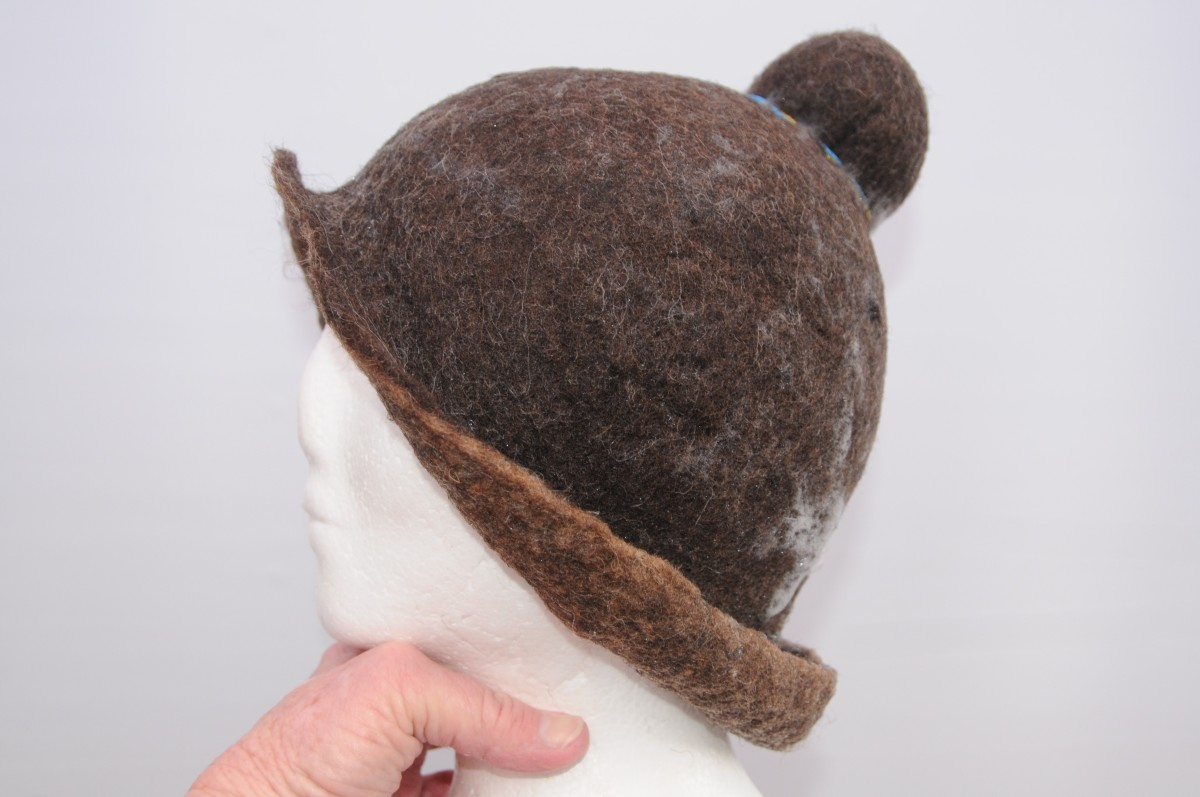 Shaping the hat to just above the eyebrows and  to the nape of the neck.