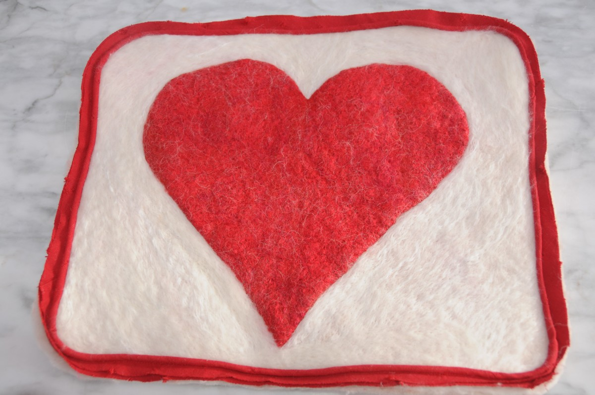 Piping sewn onto the felted cushion.