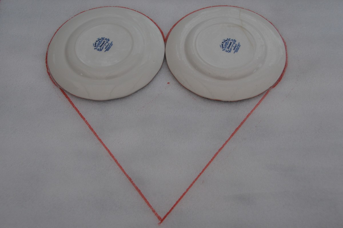 2 Saucers placed on floor underlay with the the lines drawn to make a heart.