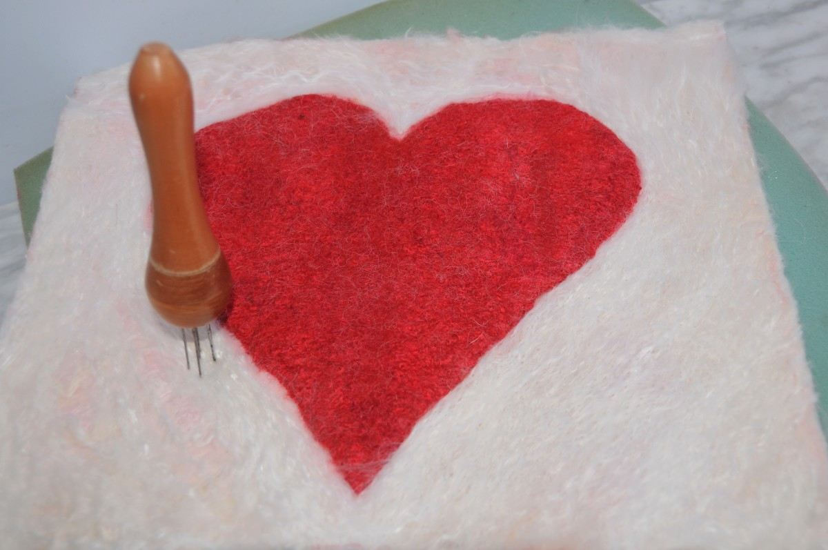 Needle felting white fiber into the pink layer of wool.