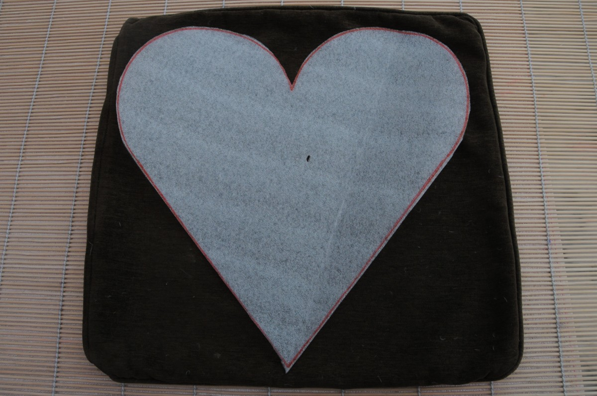 The heart should almost cover the cushion you will be using.  It will shrink during the felting process.