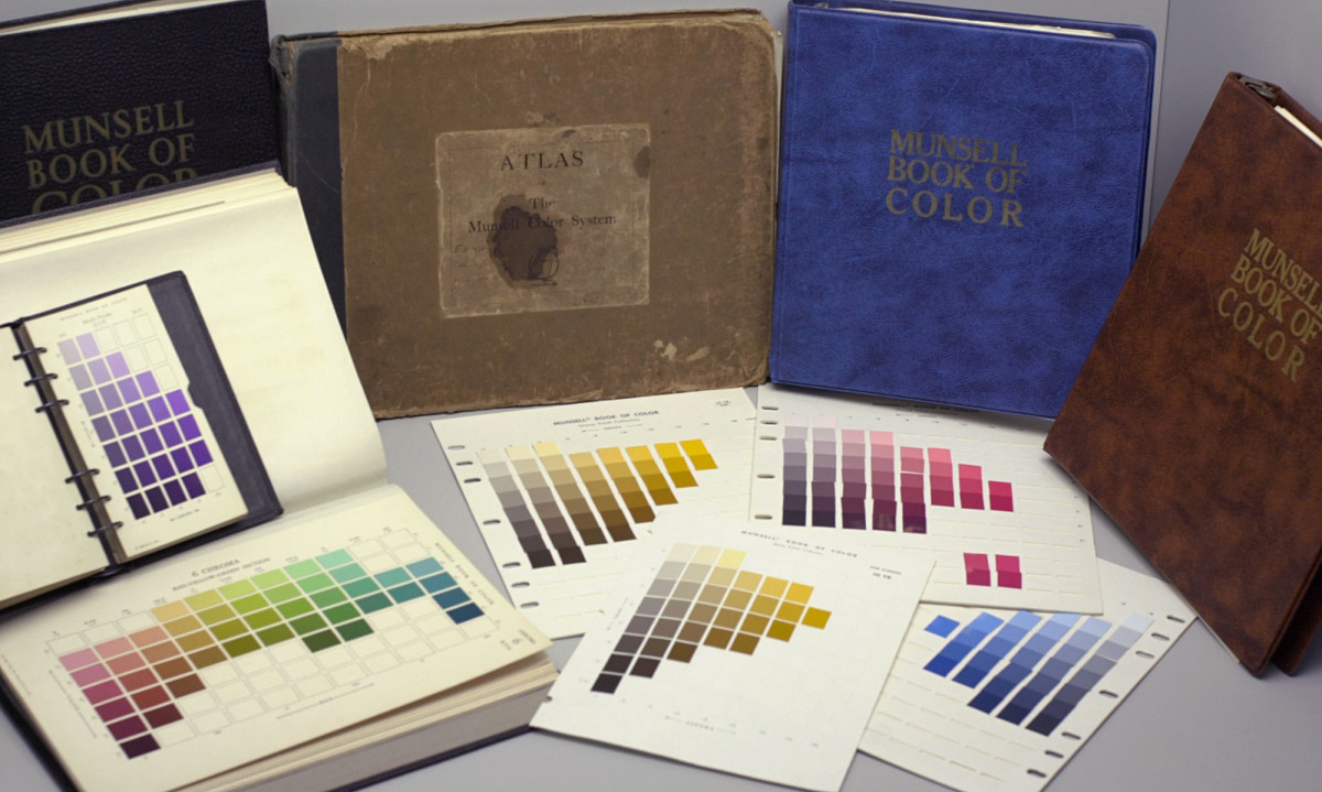 Several editions of the Munsell Book of Color, the color atlas of the Munsell color system sold by the Munsell Color Company, perched behind several of the book's removable pages of color swatches.