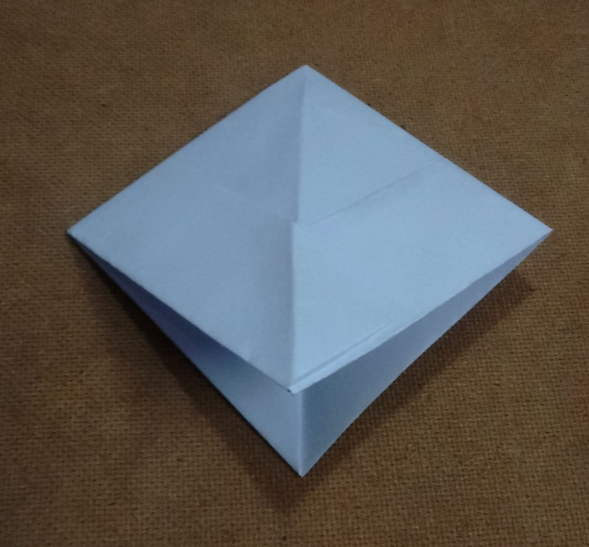 This results in the formation of a square shaped paper structure with two lower corners.
