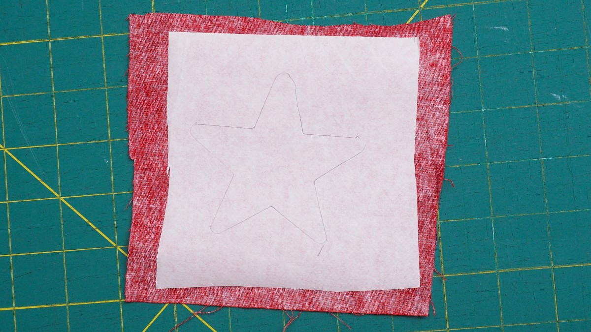 Using your star template, trace the shape onto the paper side of the fusible web that has already been placed on the fabric.
