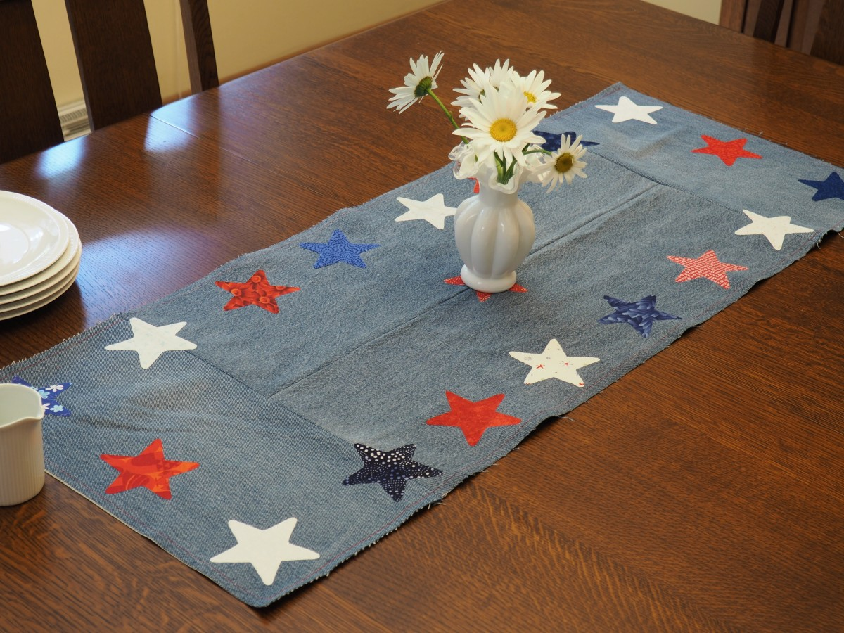 An easy-to-follow tutorial for a DIY patriotic table runner made with repurposed jeans and fabric scraps.