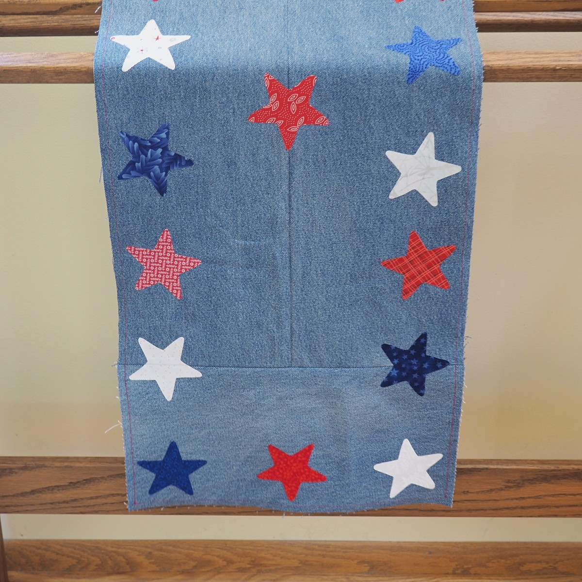 This patriotic table runner made from repurposed blue jeans and fabric scraps doesn't just have to be displayed on a table.  Hang it over a quilt rack for added color.