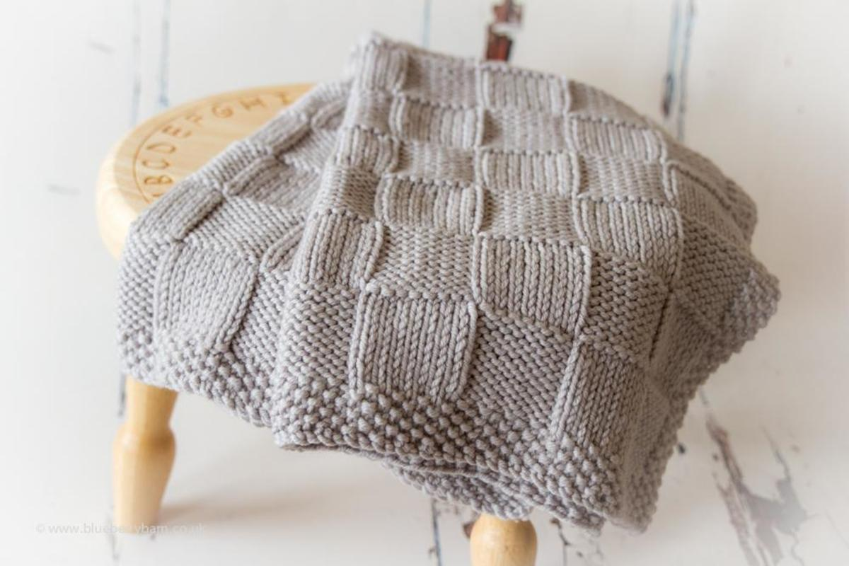A chunky knit blanket with squares and edging makes a great handmade throw blanket.