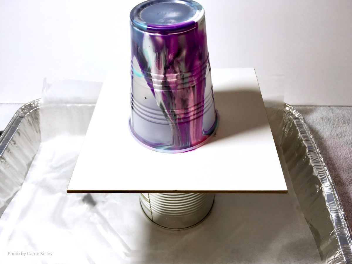 Use a metal can to raise your wood panel for a pour painting.