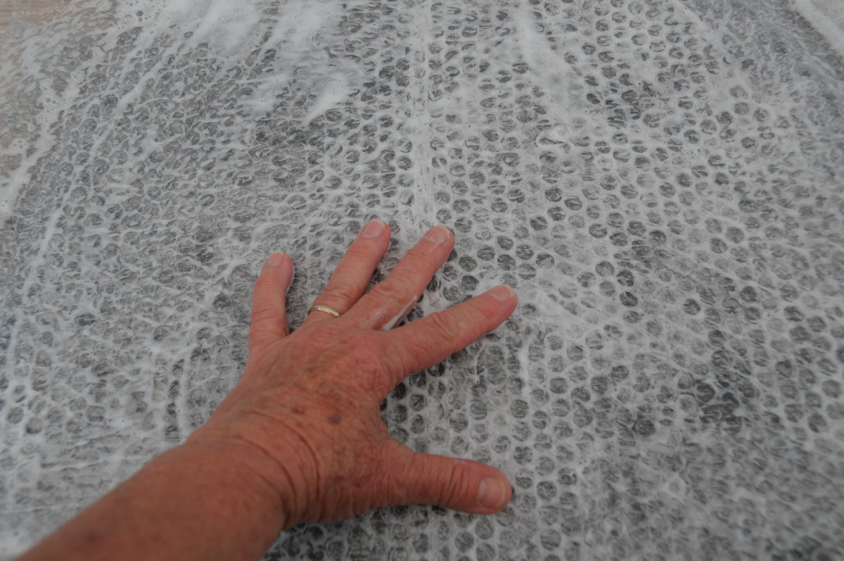 Rubbing the wet surface of the bubble wrap.