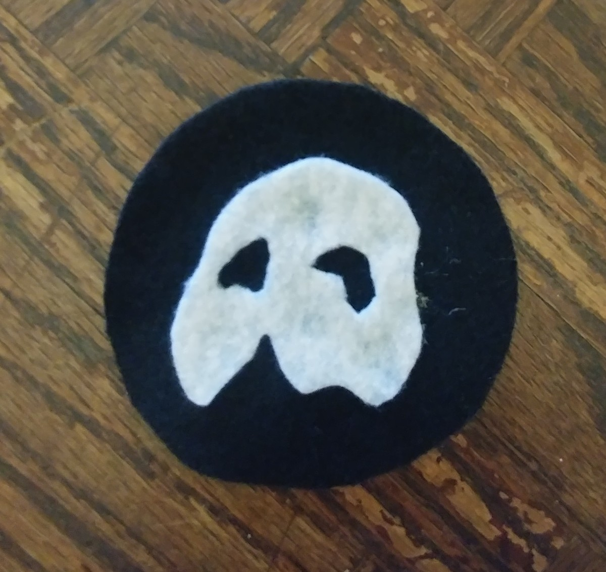 Hot glue the mask on the black circle.