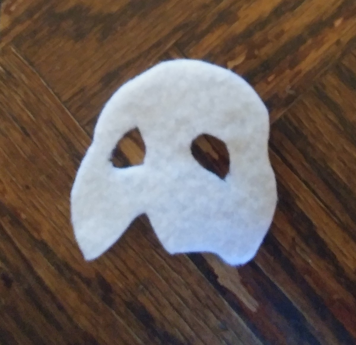 Cut the iconic white mask out of white felt.