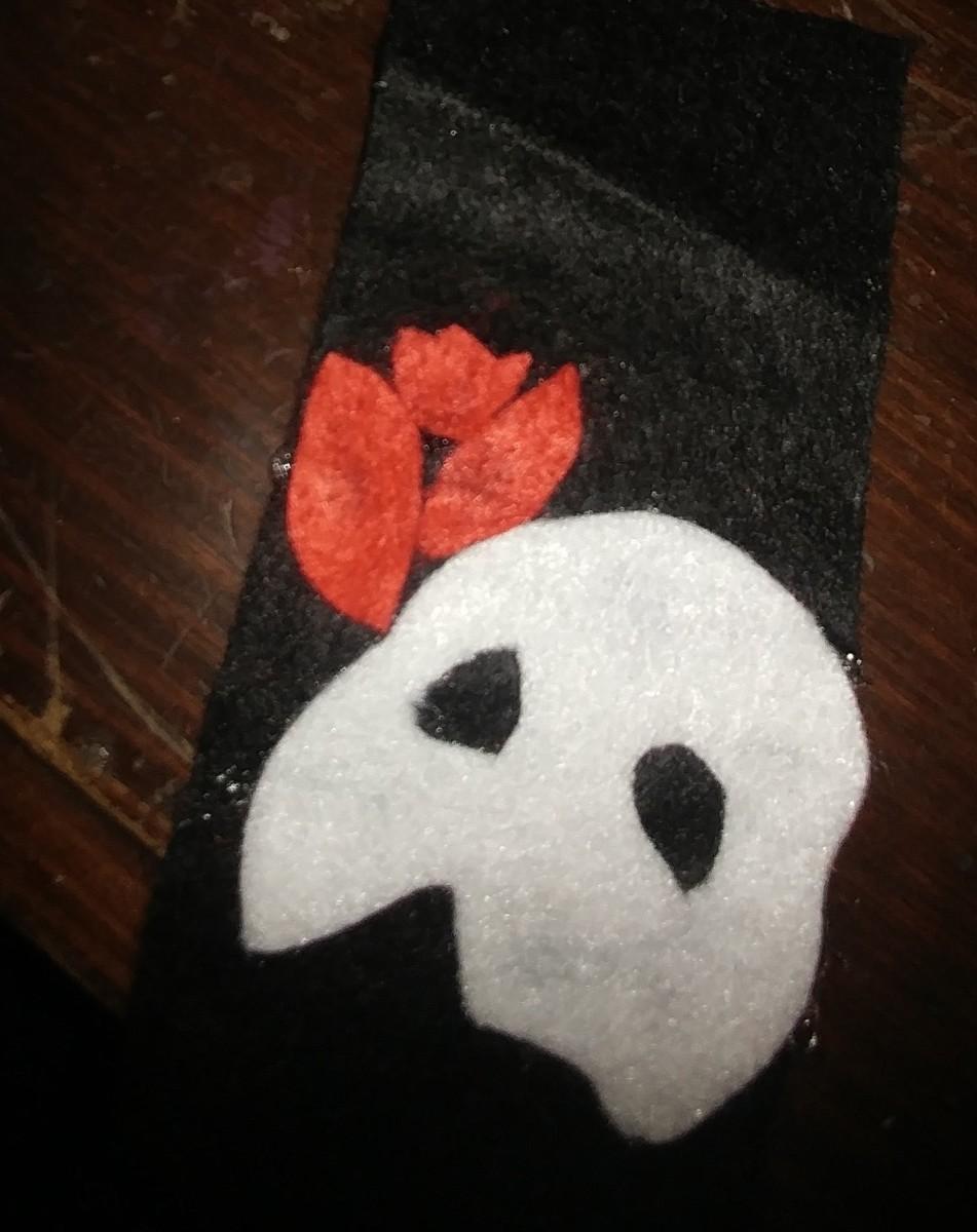 Glue red felt petals above mask, left hand side of mask.
