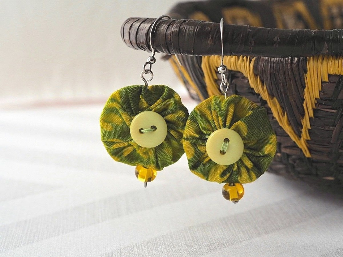 Using this easy tutorial, make your own pair of these unique yo yo earrings with a few fabric scraps, buttons, beads and jewelry making supplies.