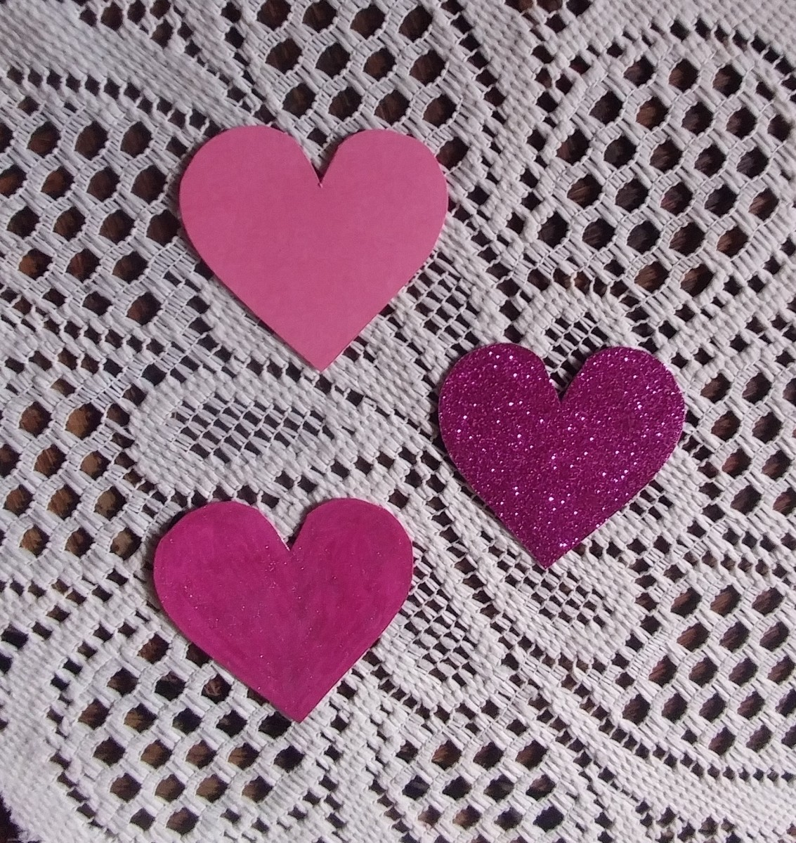 Cut hearts out of pink or red paper.