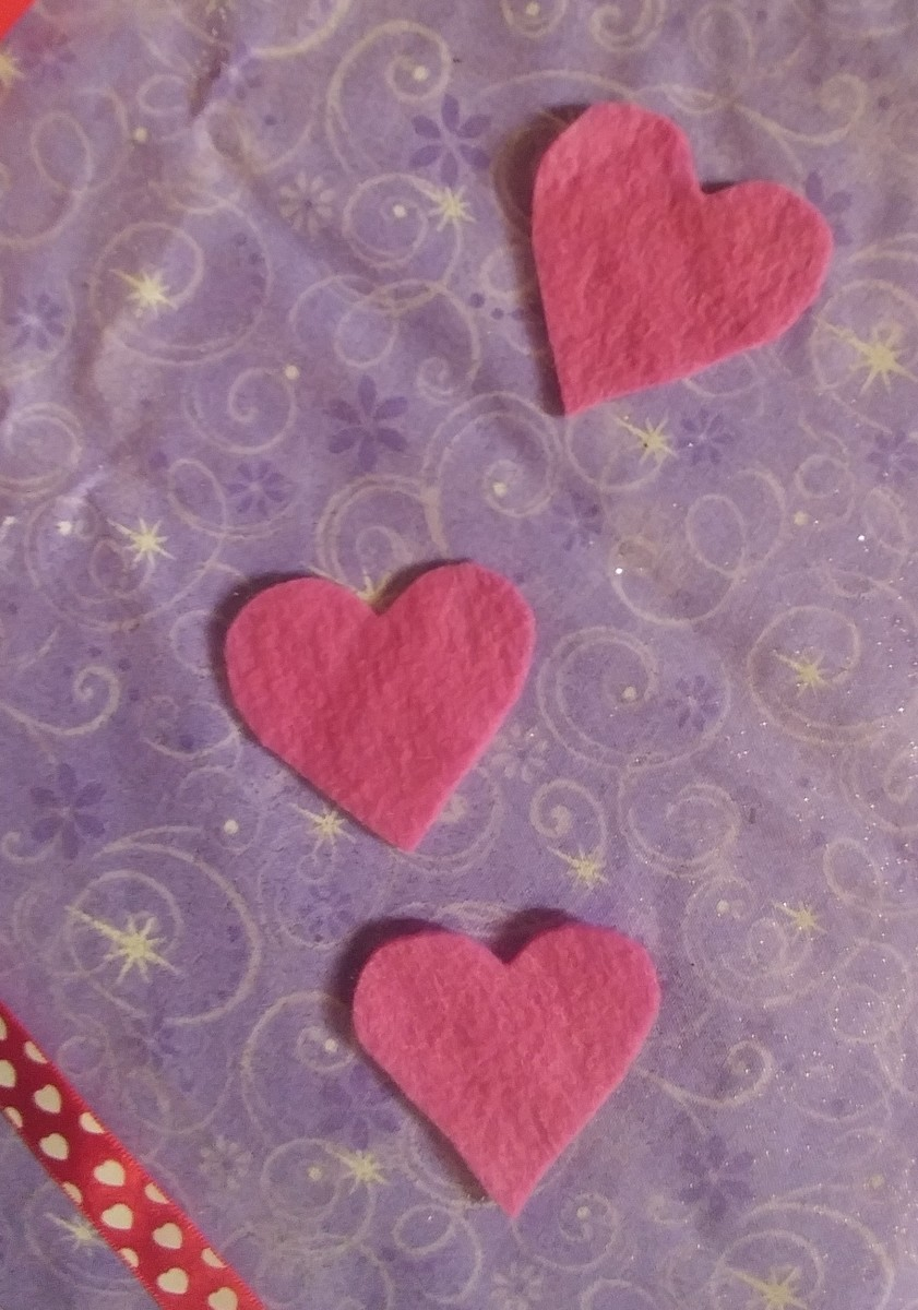 Cut three hearts out of pink felt.