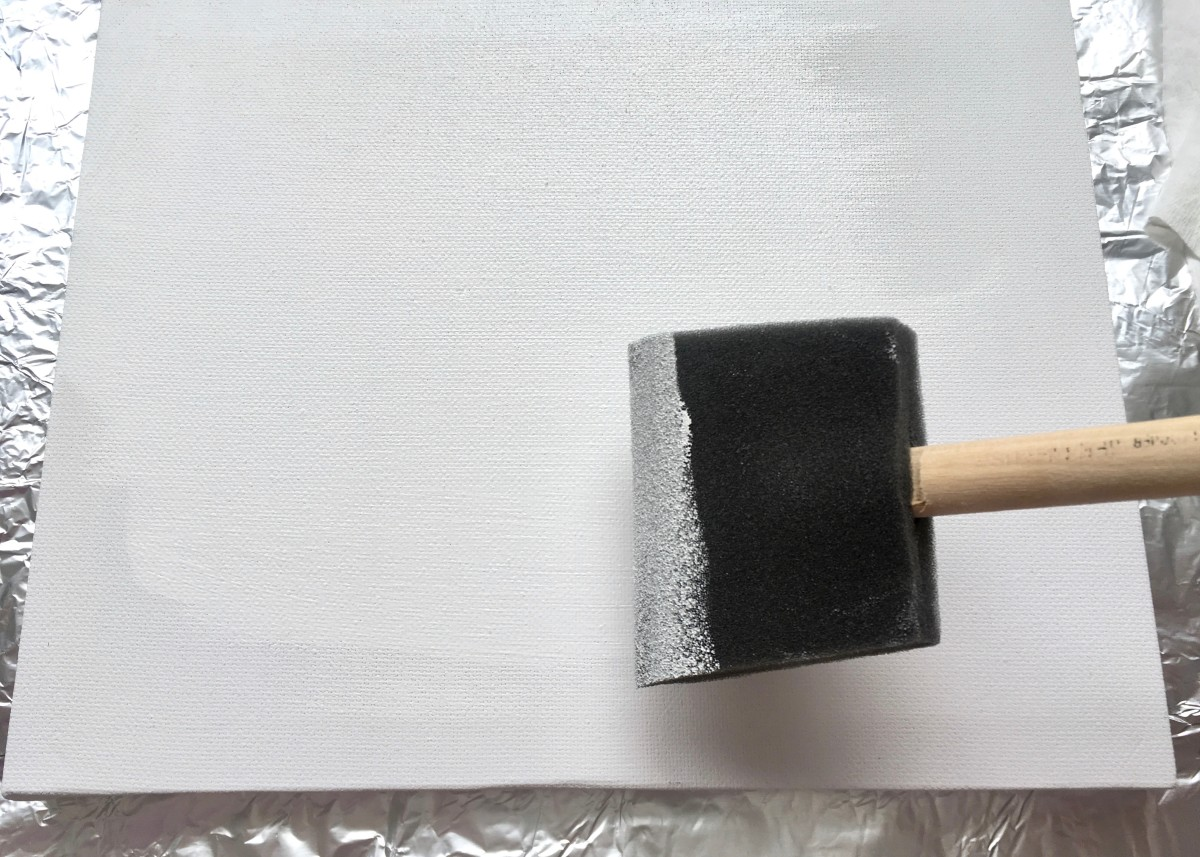 Applying a coat of gesso with a sponge brush
