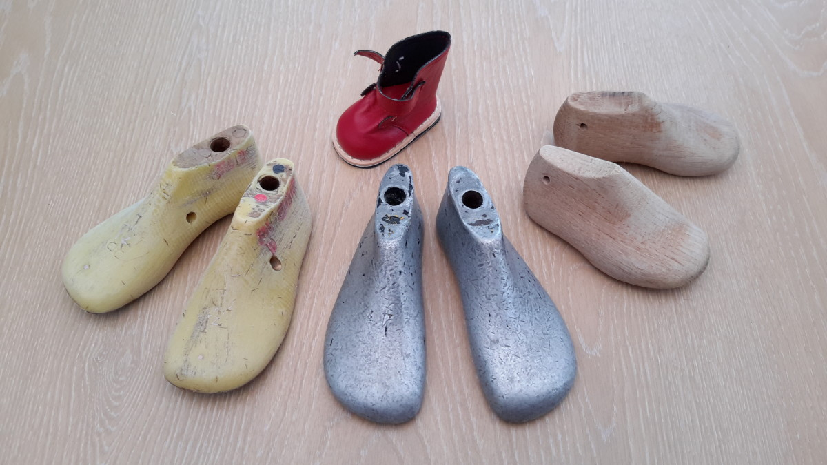 Wooden, children's metal shoe lasts and a doll's leather boot.