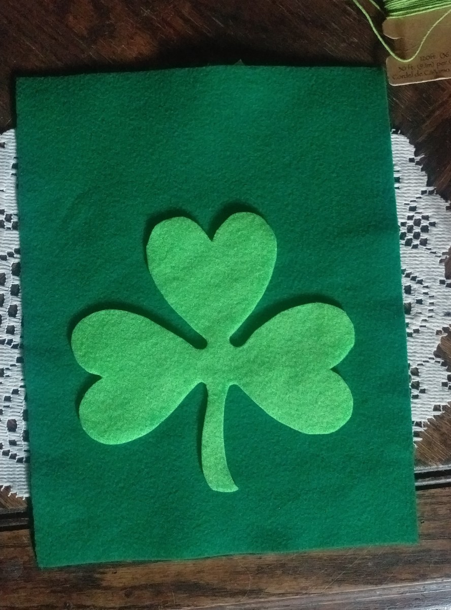 Glue shamrock on to the dark green felt sheet.