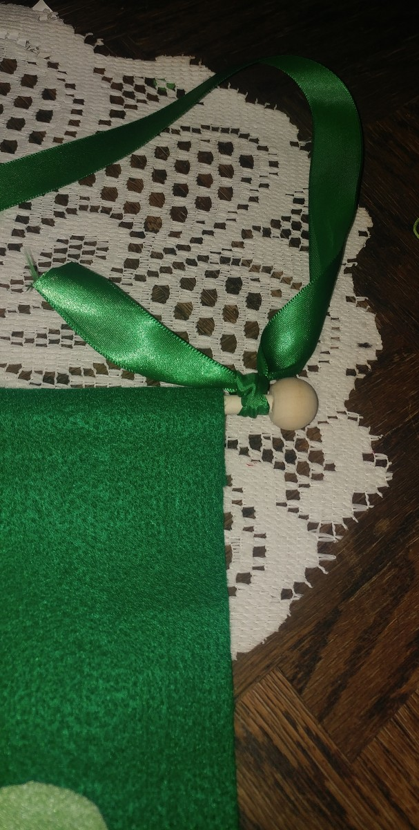 Tie green ribbon or string to both ends of dowel.