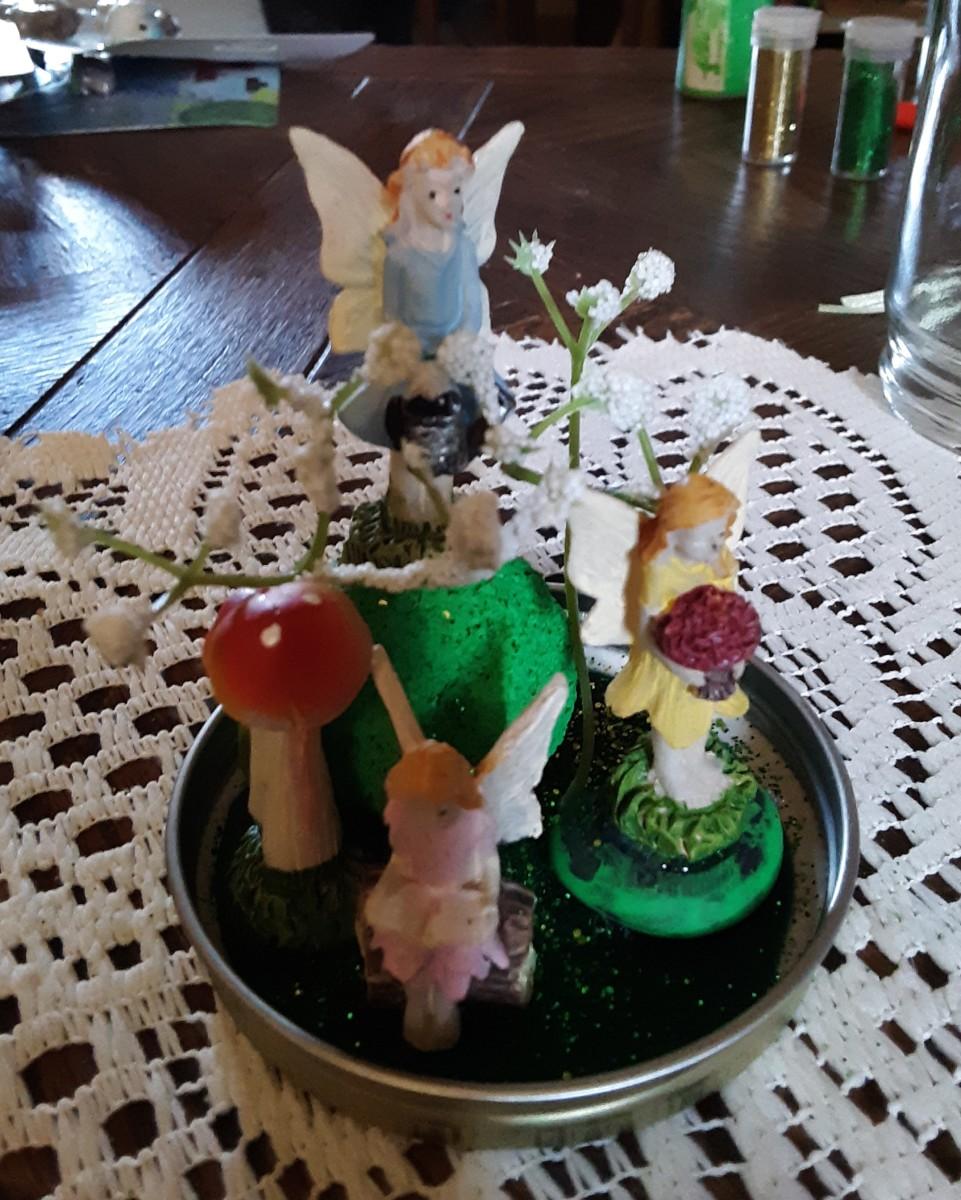 I places tiny white plants around fairy. Sprinkle glitter.