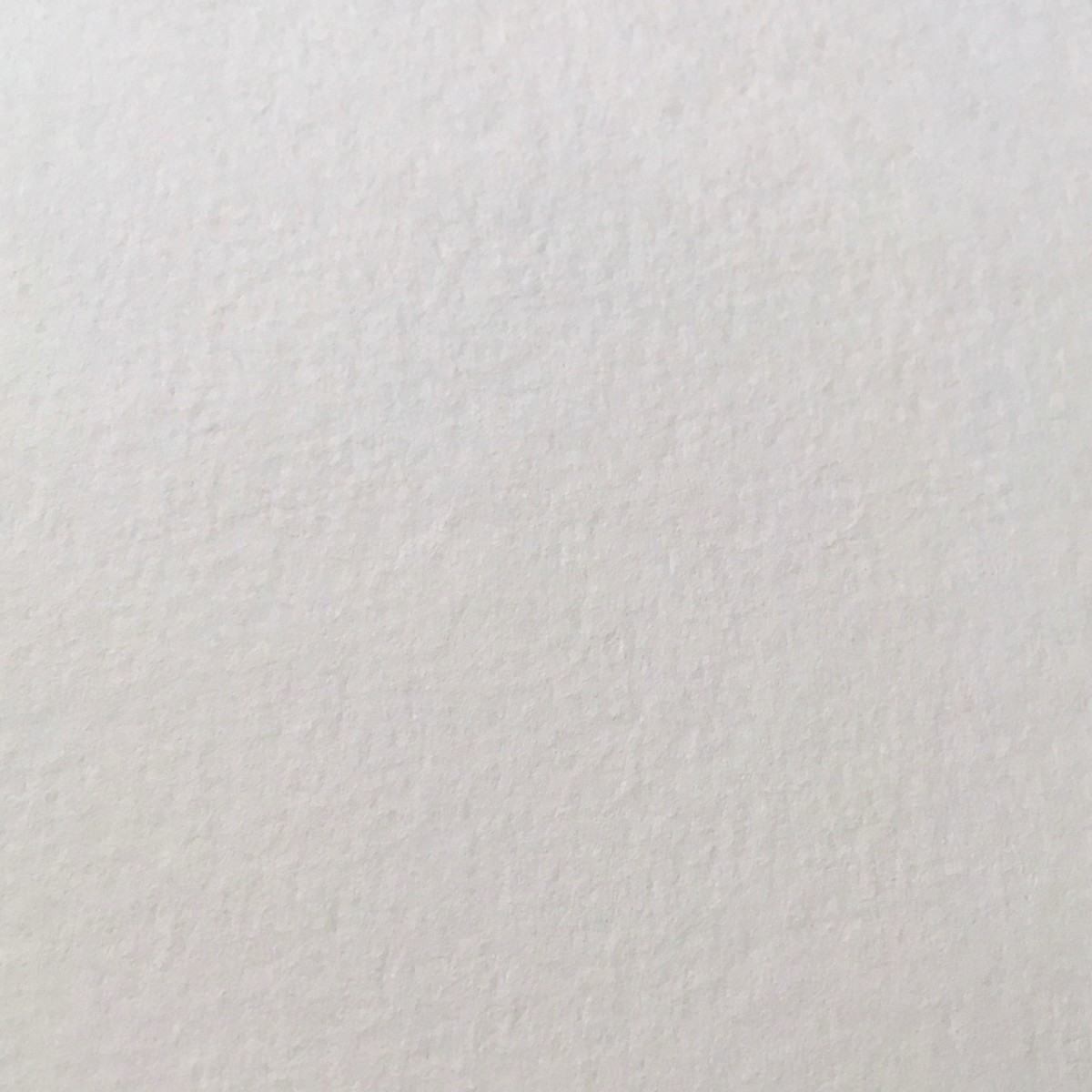 A close-up showing the texture of a sheet of cold-pressed watercolor paper