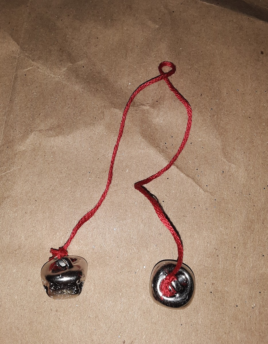 Tie little bells on red yarn or string.