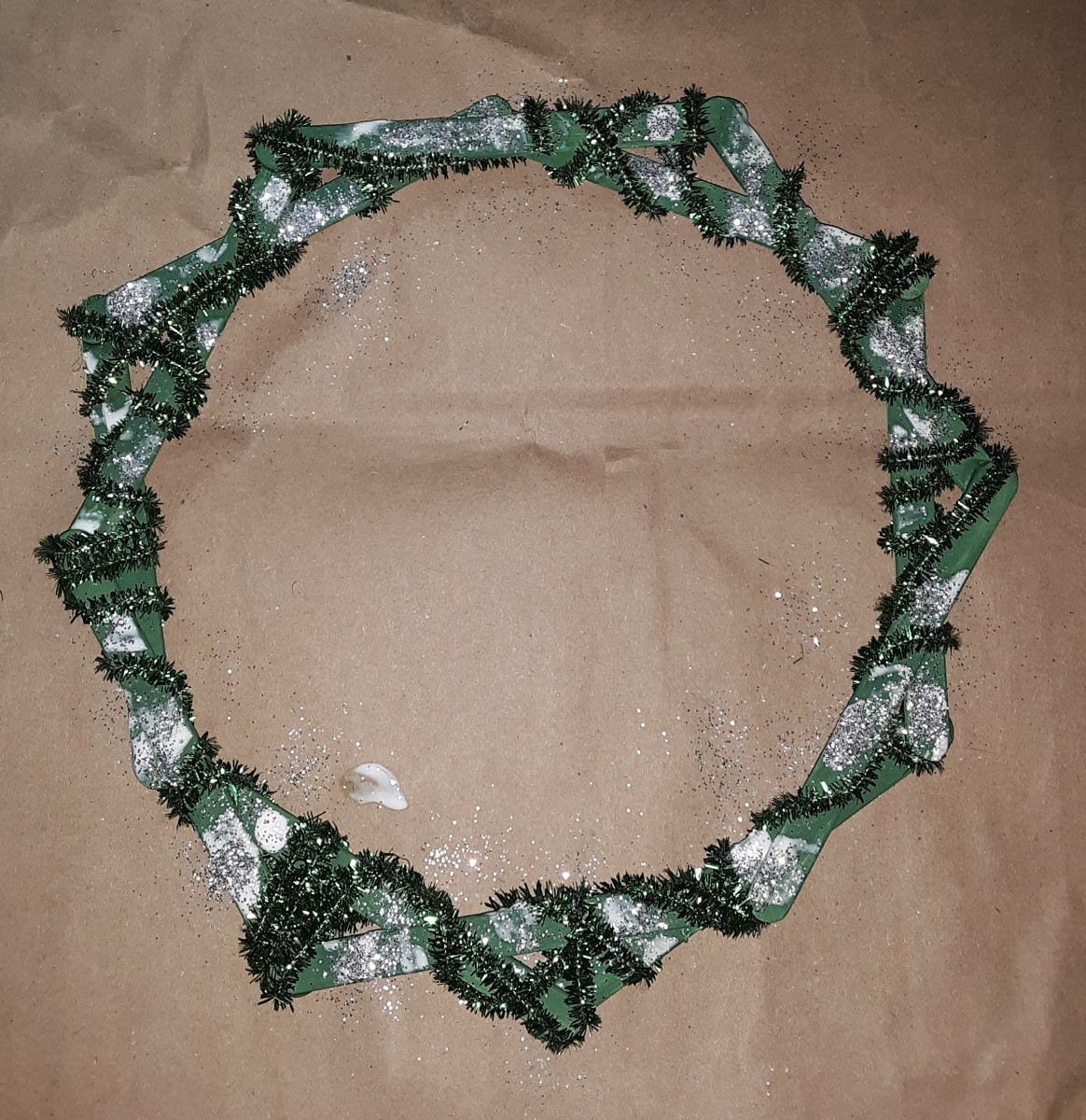 Sprinkle glitter on to Mod Podge and paint on  to the wreath. Carefully avoid fuzzy sticks.