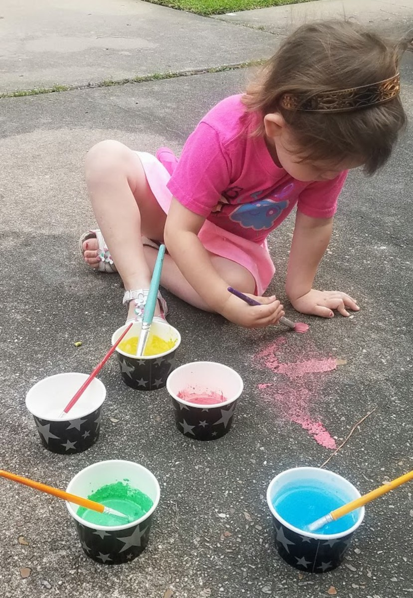 My three-year-old daughter painting with chalk paint on our driveway.