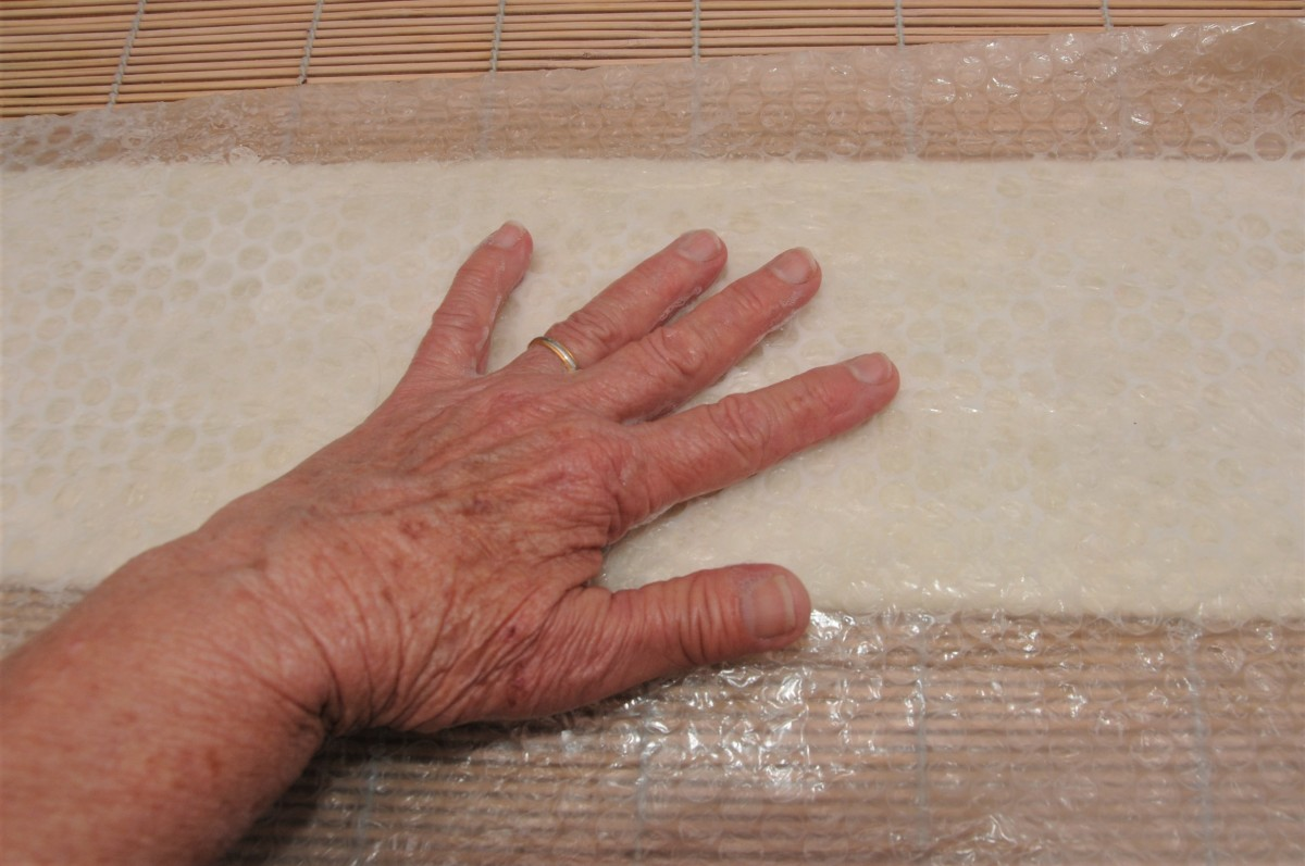 Rubbing the surface of the bubblewrap.