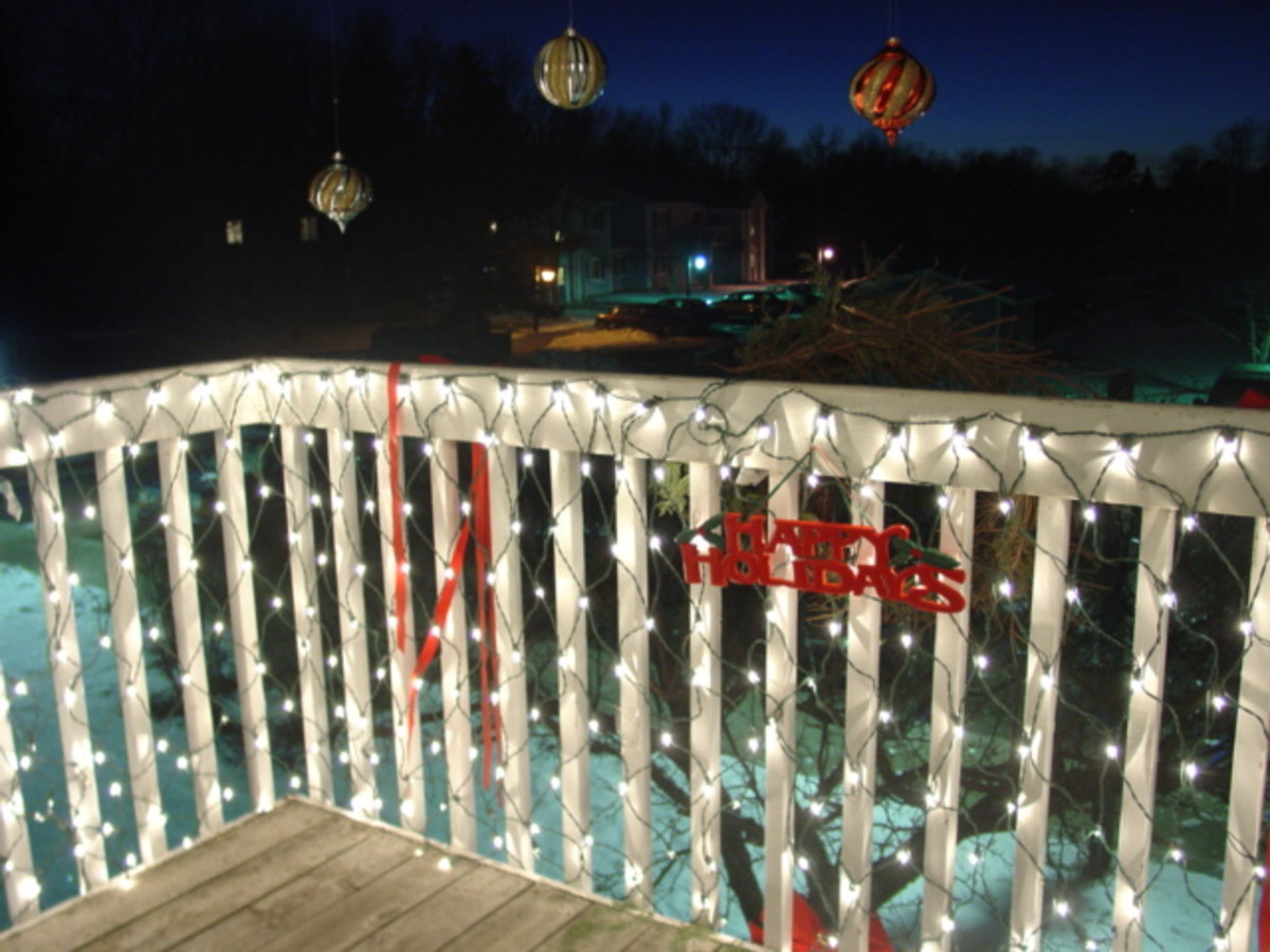A nicely lit balcony with white light, red ribbon and colored balls
