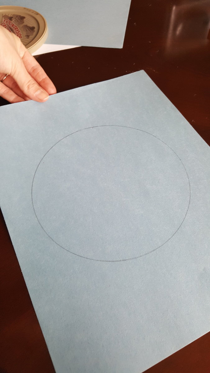 Draw a big circle on a blue sheet of construction paper. I traced a lid.