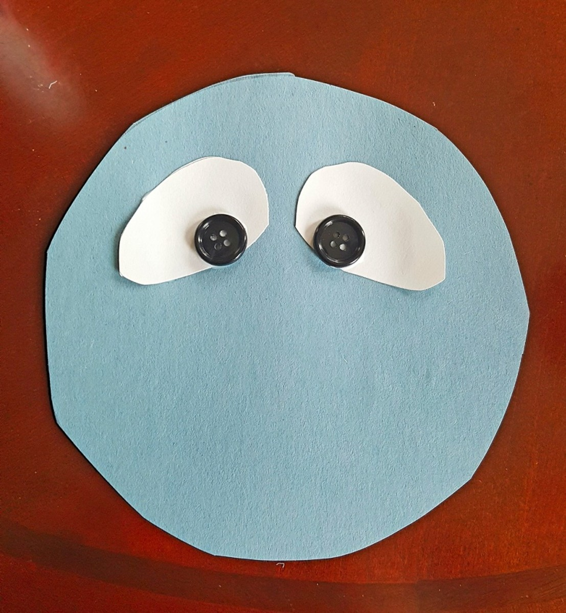 Glue two white ovals and black buttons onto your circle to make Bumble's eyes.