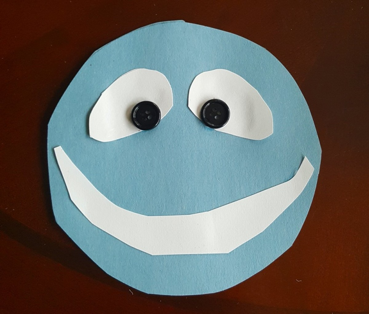 Glue a white semi circle onto your blue circle to make teeth.