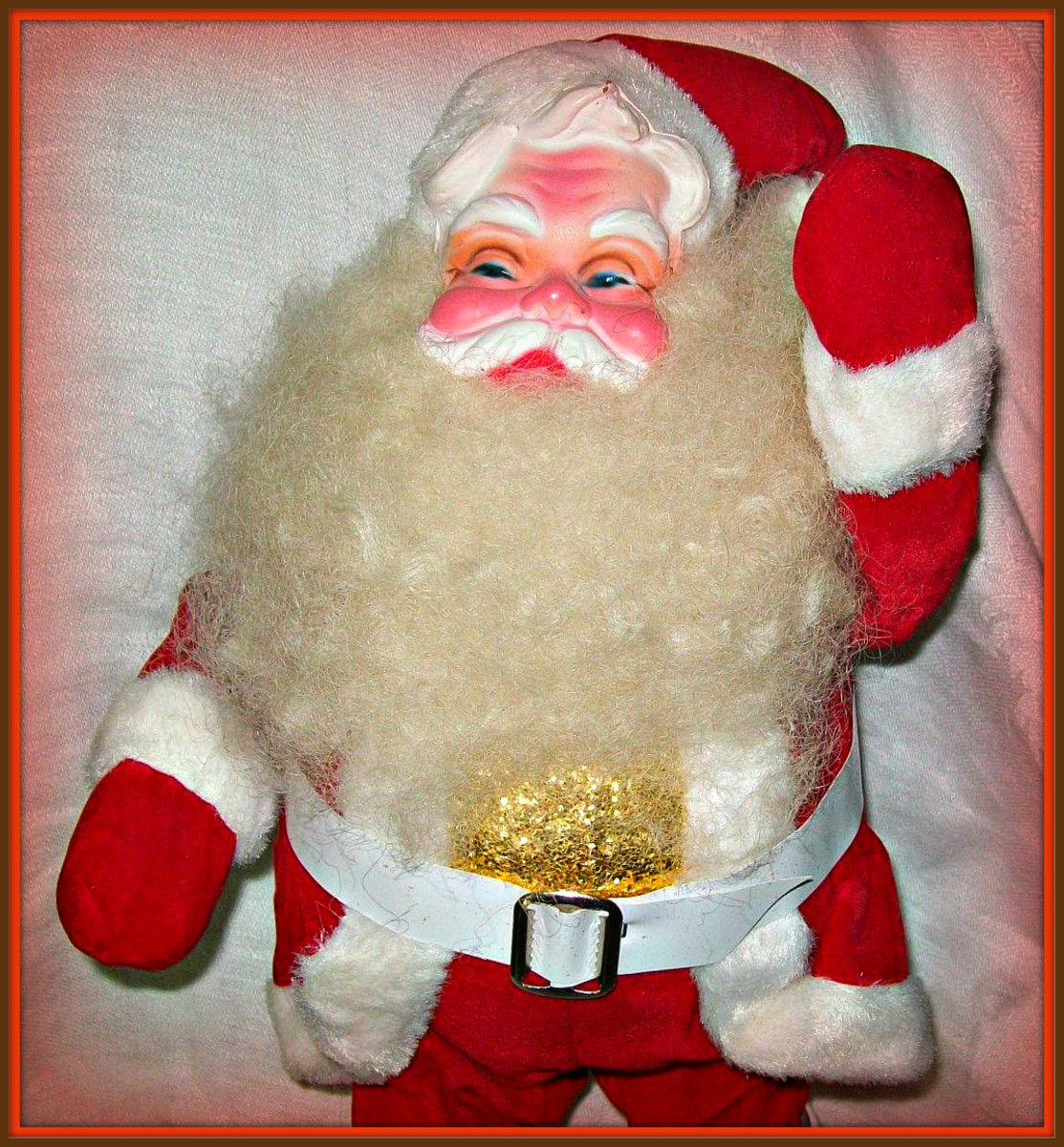 This vintage Santa measures about 14 inches tall. He is in his red velvet suit, with white trim, belt and boots. He is wearing a gold shirt under his coat.