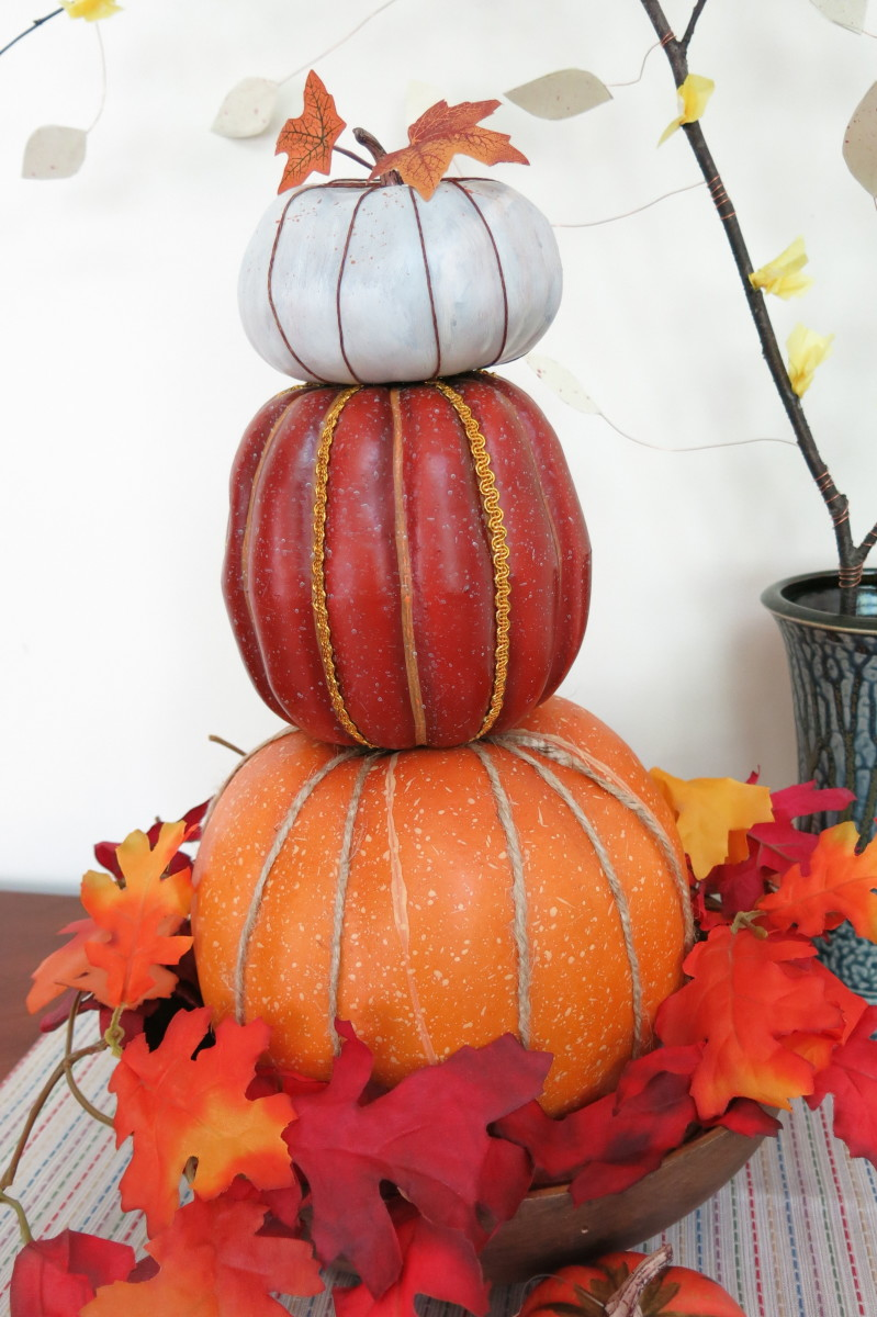 You can use a stacked pumpkin topiary as a centerpiece for your autumn table.