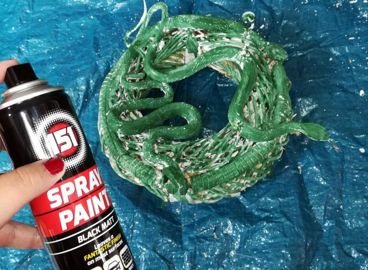 Once the snakes are attached, you can begin painting the wreath.
