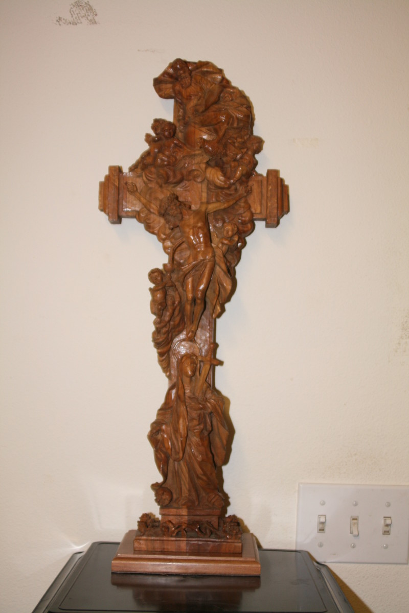 A cross made from German Walnut with may religious symbols on it.