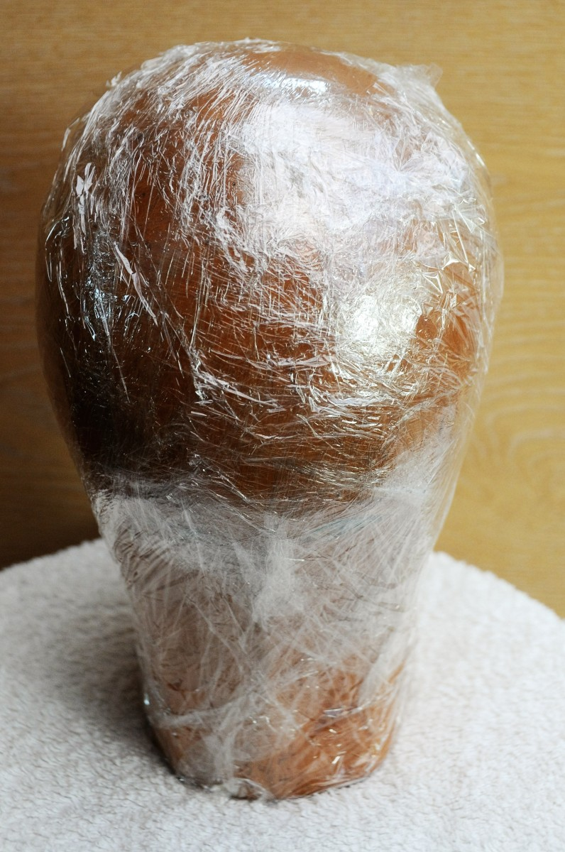 Hat block covered in cling wrap